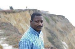 Schwarzer Mann an der Küste Stockbild