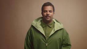 Schwarzer Mann der Mischrasse auf beige Hintergrund im Studioporträt stock video