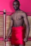 Schwarzer Mann, der nahe einem Reedschirm aufwirft Stockfotos