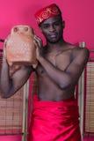 Schwarzer Mann, der nahe einem Reedschirm aufwirft Stockfotografie