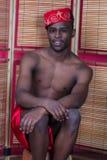 Schwarzer Mann, der nahe einem Reedschirm aufwirft Lizenzfreies Stockfoto