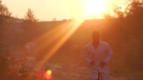 Schwarzer Mann, der in Richtung zum Sonnenuntergang, Sonnenaufgang läuft stock video footage