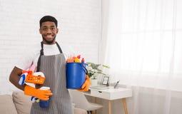 Schwarzer Mann, der Schwämme und Reinigungsmittel in waschenden Handschuhen hält lizenzfreie stockfotos