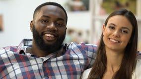 Schwarzer Mann, der seine hübsche Freundin, die Paare sitzen auf Sofa und das Umarmen betrachtet stock footage