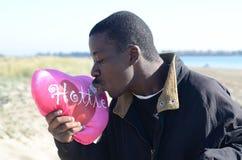 Schwarzer Mann, der seinen Valentinsgruß küsst Lizenzfreies Stockbild
