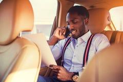 Schwarzer Mann, der Smartphone in einem Auto verwendet stockbild