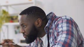 Schwarzer Mann, der unangenehmem Geschmack glauben und Geruch, der Abendessen, verdorbene Nahrung, GVO isst stock video