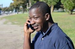 Schwarzer Mann am Handy Stockbild