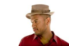 Schwarzer Mann im roten Hemdbrown-Hut, der recht schaut lizenzfreies stockbild