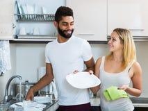 Schwarzer Mann mit Abstauben der weißen Frau in der inländischen Küche Stockfotos