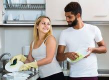 Schwarzer Mann mit Abstauben der weißen Frau in der inländischen Küche Stockbilder