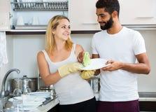 Schwarzer Mann mit Abstauben der weißen Frau in der inländischen Küche Lizenzfreie Stockfotografie