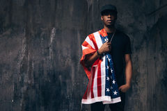 Schwarzer Mann mit amerikanischer Flagge auf Schulter Stockfotos