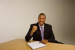 Schwarzer Mann mit Auflage am Schreibtisch mit der angehobenen Faust lizenzfreies stockbild