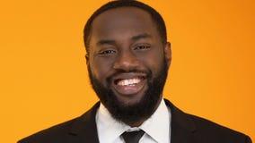 Schwarzer Mann mit dem gesunden Lächeln, das die Kamera lokalisiert auf gelbem Hintergrund untersucht stock footage