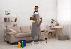 Schwarzer Mann mit Moppreinigungsboden zu Hause stockbilder
