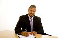 Schwarzer Mann-Schreiben am Schreibtisch und Betrachten der Kamera lizenzfreie stockbilder