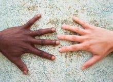 Schwarzer Mann und weißes weibliches Handerreichen Stockfotos