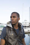 Schwarzer Mann weit, der weg dem Bootsjachthafen betrachtet Lizenzfreies Stockbild