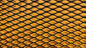 Schwarzer metallischer Grill auf orange Papierhintergrund stock abbildung