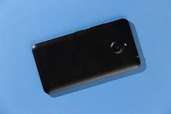 Schwarzer moderner Smartphone auf blauem Hintergrund Stockbilder