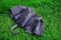 Schwarzer nasser Regenschirm auf grünem Gras Lizenzfreie Stockfotos