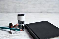 Schwarzer Notizblock, Bleistiftspitzer, Bleistift, elastisch auf einem Licht zurück Stockbilder