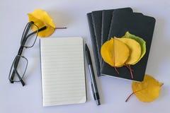 Schwarzer Notizblock für Anmerkungen und Gelb verlässt auf einem weißen Hintergrund Lizenzfreies Stockbild