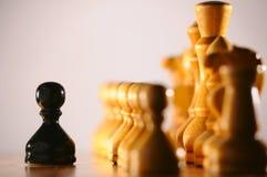 Schwarzer Pfandgegenstand gegen weiße Schachstücke lizenzfreies stockbild