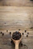 Schwarzer Pfeffer auf hölzernem Hintergrund Lizenzfreie Stockbilder