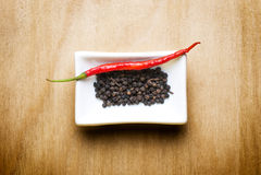 Schwarzer Pfeffer des glühenden Paprikas auf hölzerner Tabelle lizenzfreies stockbild