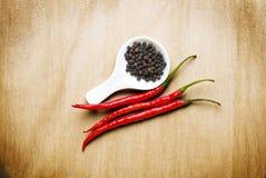 Schwarzer Pfeffer des glühenden Paprikas auf hölzerner Tabelle lizenzfreies stockfoto