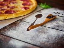 Schwarzer Pfeffer in einem hölzernen Löffel auf dem Küchentisch stockfotografie