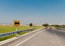 Schwarzer Pfeil auf gelbem Verkehrszeichen neben Straße nahe durch grünes ric Lizenzfreie Stockfotografie