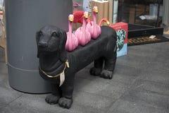 Schwarzer Plastikdachshundhund mit rosa Flamingos auf der Rückseite Lizenzfreie Stockfotos