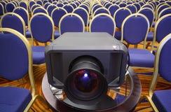 Schwarzer Projektor in der Mitte von Reihen der Stühle Stockfotografie