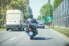 Schwarzer Radfahrer mit dem Motorrad, das auf Landstraße fährt Lizenzfreies Stockfoto