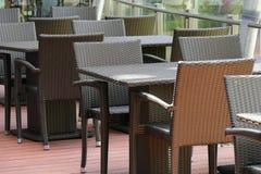 Schwarzer Rattantisch und Stuhl auf der Terrasse Lizenzfreies Stockfoto