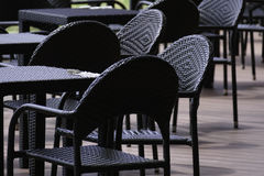 Schwarzer Rattantisch und Stuhl auf der Terrasse Stockbild