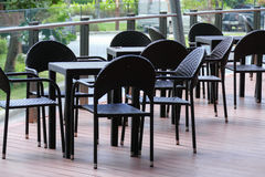 Schwarzer Rattantisch und Stuhl auf der Terrasse Stockfotografie