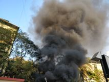 Schwarzer Rauch, der aus ein Gebäude auf Feuer herauskommt stockfotografie