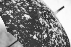 Schwarzer Regenschirm und weißer Schnee demgegenüber Stockbild