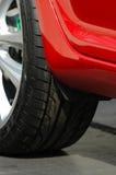 Schwarzer Reifen eines roten Autos Stockfoto
