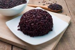 Schwarzer Reis kochte auf weißer den organischen Platte und schwarzen Reiskörnern Lizenzfreie Stockfotografie