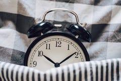 Schwarzer Retro- Wecker schlafend auf Kissen mit der umfassenden Metapher von Schlaflosigkeit, spät bei der Arbeit, wohlem Schlaf stockbild
