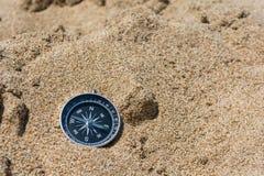 Schwarzer Richtungskompaß auf goldenem Sand Fokus auf Kompass lizenzfreies stockbild