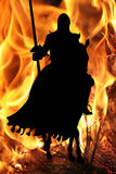 Schwarzer Ritter auf einem Pferd auf einem Flammehintergrund Stockbilder