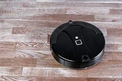 schwarzer Roboterstaubsauger läuft auf Laminatboden Roboter gesteuert durch Sprachsteuerungen für direkte Reinigung Modernes inte lizenzfreie stockfotografie