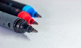 Schwarzer, roter und blauer Stift auf weißem Hintergrund Lizenzfreie Stockfotos