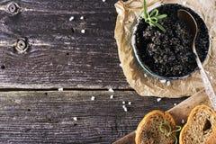 Schwarzer russischer gesalzener Störkaviar Astrakhans in einer Dose auf dunklem Hintergrund mit hölzernem Löffel und Scheiben bro Lizenzfreie Stockfotos